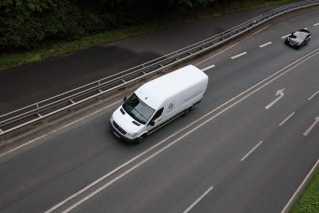 Weißer Mercedes-Sprinter auf Straße von oben