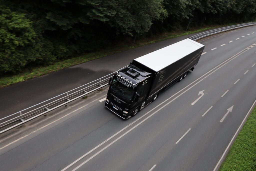 Schwarzer LKW auf der Autobahn von oben