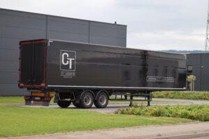 Schwarzer LKW-Anhänger vor Logistikgebäude