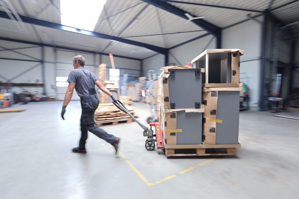 Mitarbeiter zieht mit einem Hubwagen, verpackte Ware durch die Lagerhalle