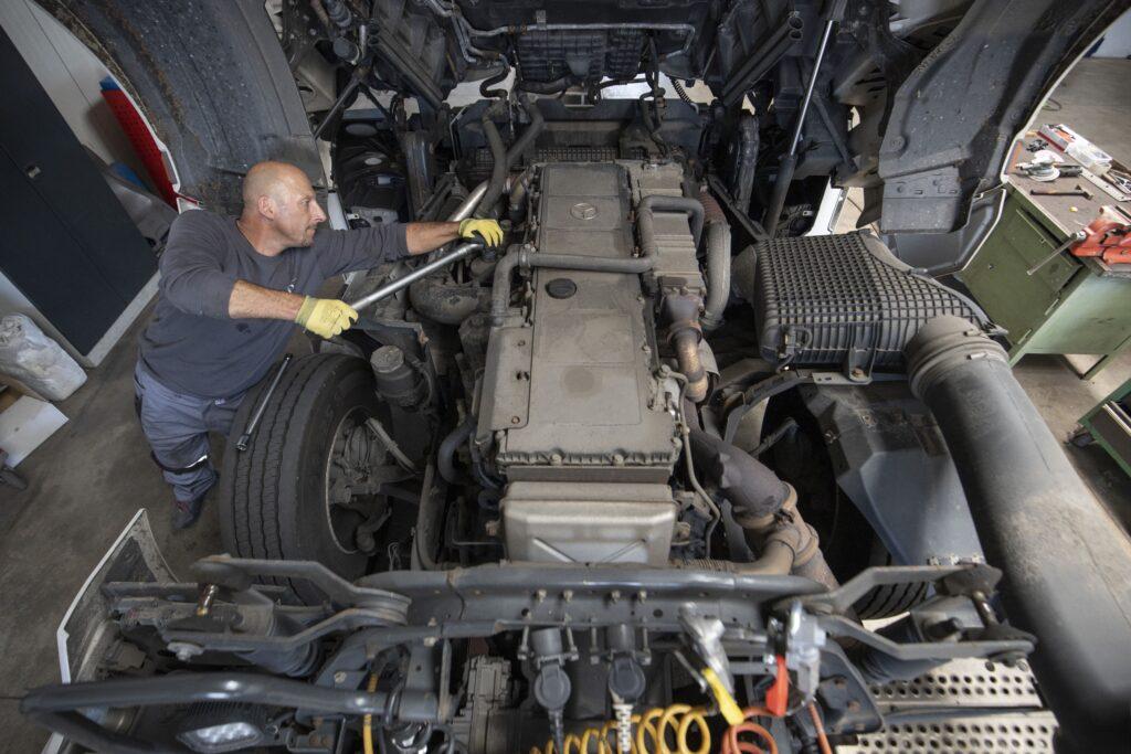 Monteuer repariert den Motor eines LKW's
