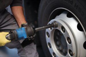 Mitarbeiter wechselt den Reifen an einem LKW